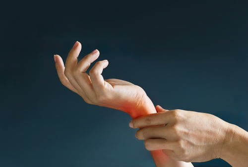 Acute pain in a woman wrist, colored in red on dark blue backgro